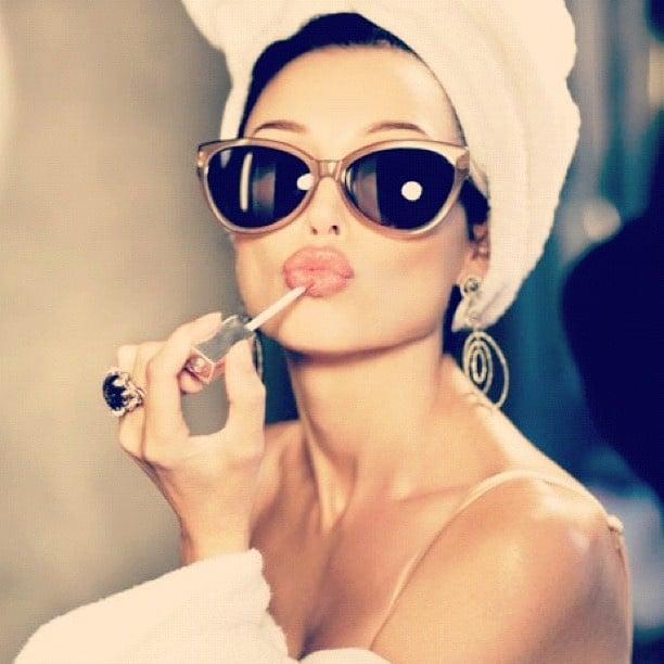 Woman Applying Lip Gloss with Sunglasses and Turban On