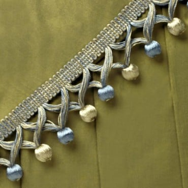 Add a unique touch to your home furnishings with our Covered Beaded Fringe. The fringe is made with an overlapping criss-cross design that features covered round beads at the bottom of the trim. The braided guimp attached to the fringe can easily be sewn